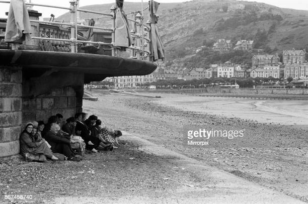 Llandudno, a seaside town in Conwy County Borough, Wales. Holiday makers taking shelter from the bad weather, 16th July 1958.