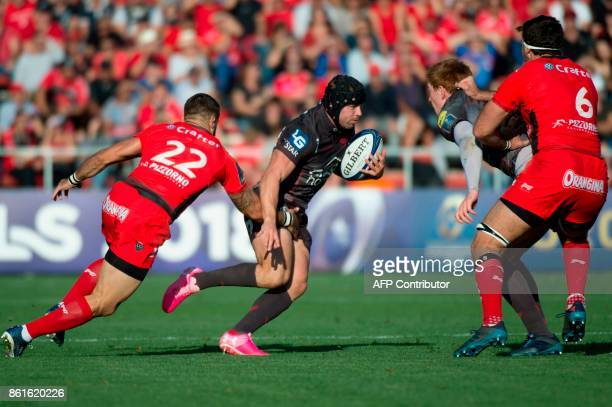 Llanelli Scarlets fullback Leigh Halfpenny avoids the tackle from RC Toulon's French scrumhalf Sebastien TillousBorde during the European Champions...