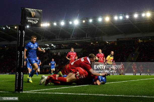 Llanelli , United Kingdom - 8 September 2018; Fergus McFadden of Leinster goes over to score his side's first try despite the tackle of Leigh...