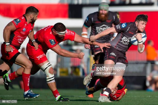 Llanelli's Welsh fullback Steffan Evans avoids a tackle from RC Toulon's defenders during the European Champions Cup rugby union match between RC...