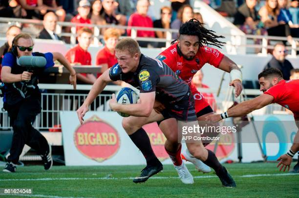Llanelli's Welsh winger Johnny McNicholl attempts to avoid a tackle from RC Toulon's New Zealander centre Maa Nonu and RC Toulon's French scrumhalf...