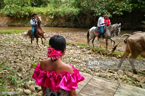 Llanera woman stares at Colombian cowboys crossing a small creek on horses