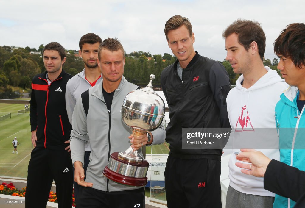 Lleyton Hewitt of Australia hands back the Kooyong Classic trophy after a photocall as Gilles Simon of France, Grigor Dimitrov of Bulgaria, Tomas Berdych of Czech Republic, Richard Gasquet of France and Kei Nishikori of Japan look on during a press conference ahead of the AAMI Classic at Kooyong on January 7, 2014 in Melbourne, Australia.