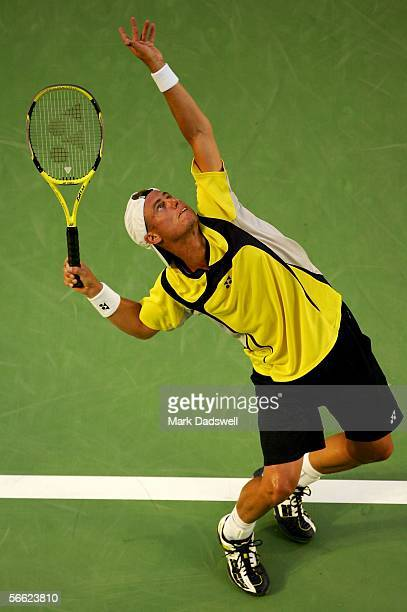Lleyton Hewitt of Australia hits a serve in his second round match against Juan Ignacio Chela of Argentina during day four of the Australian Open at...