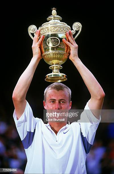 Lleyton Hewitt of Australia lifts the trophy after victory over David Nalbandian of Argentina in the Men's Singles Final of the Lawn Tennis...