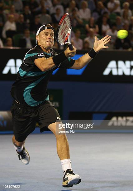 Lleyton Hewitt of Australia plays a forehand his first round match against David Nalbandian of Argentina during day two of the 2011 Australian Open...