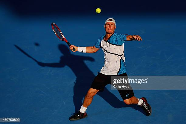 Lleyton Hewitt of Australia plays a forehand in his mens final match against Roger Federer of Switzerland during day eight of the 2014 Brisbane...