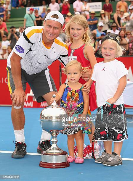 Lleyton Hewitt of Australia poses with the winners trophy and his children Ava Hewitt Cruz Hewitt and Mia Hewitt after winning his match against Juan...