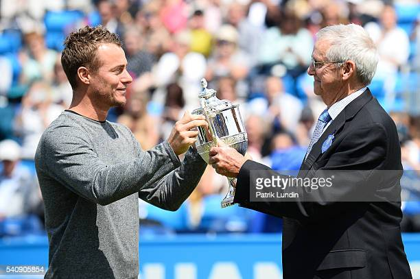 Lleyton Hewitt of Australia presents Roy Emerson of Australia with a trophy during the fourtime champions presentation on day 5 at Queens Club on...