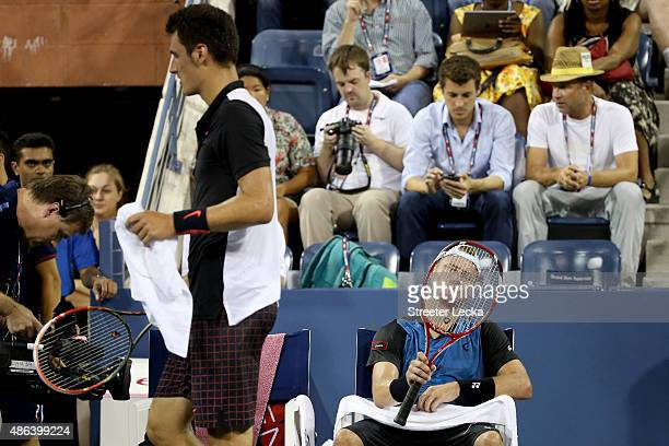 Lleyton Hewitt of Australia sits during a break in play as Bernard Tomic of Australia walks past during their Men's Singles Second Round match on Day...