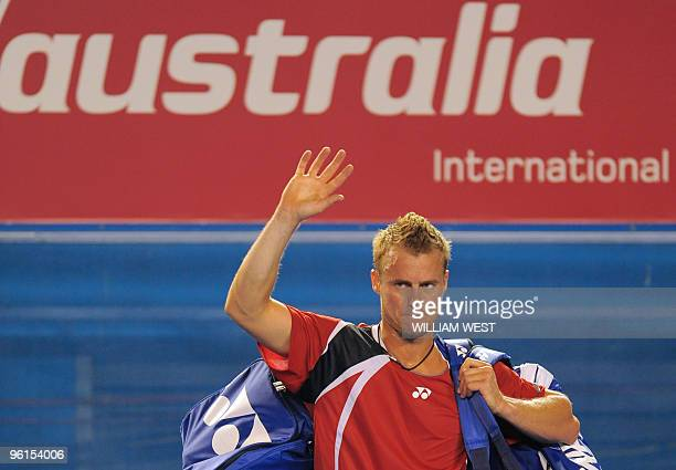 Lleyton Hewitt of Australia waves goodbye to the crowd after losing to Roger Federer of Switzerland shakes hands with Lleyton Hewitt of Australia...