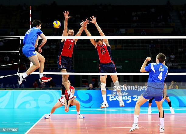 Lloy Ball and Thomas Hoff of the United States try to block a spike from Milos Nikic of Serbia as Bojan Janic watches during the volleyball event at...
