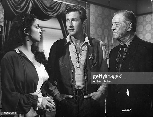 Lloyd Bridges and Tom London urge Katy Jurado to remain in Hadleyville in a scene from the film 'High Noon' 1952
