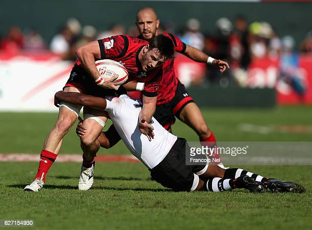 Lloyd Evans of Wales is tackled by Osea Kolinisau of Fiji during day two of the Emirates Dubai Rugby Sevens - HSBC World Sevens Series on December 2,...