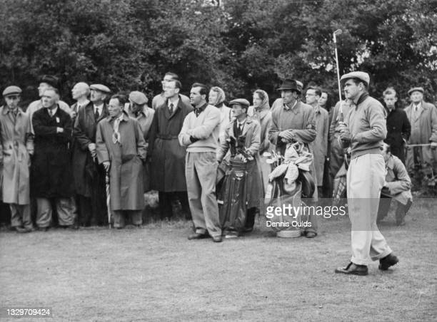 Lloyd Mangrum of the United States plays an iron shot off the 12th tee as opponent Max Faulkner and the spectators look on during the News of the...