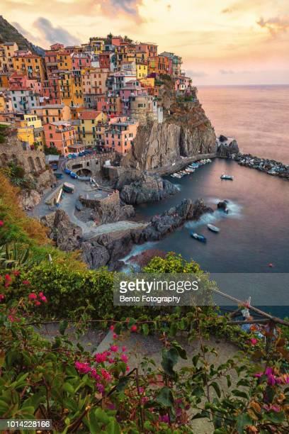 lluminated manarola town by sea against sky during sunset - liguria fotografías e imágenes de stock