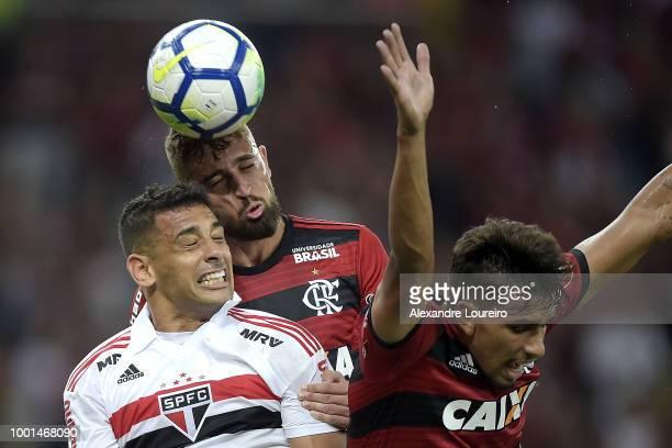Léo Duarte and Lucas Paqueta of Flamengo struggles for the ball with Diego Souza of Sao Paulo during the match between Flamengo and Sao Paulo as part...