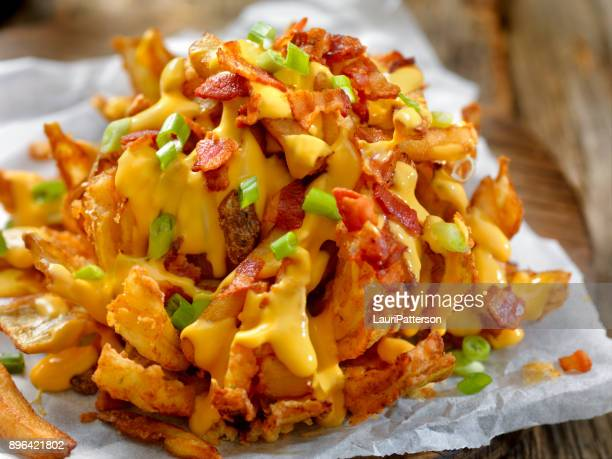 loaded blooming onion with fries, cheese sauce and bacon - cheese sauce stock photos and pictures