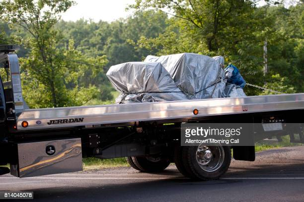A loaded flat bed truck leaves the property in Bucks County off of Lower York Road in Solebury on Wednesday July 12 2017 Investigators are searching...