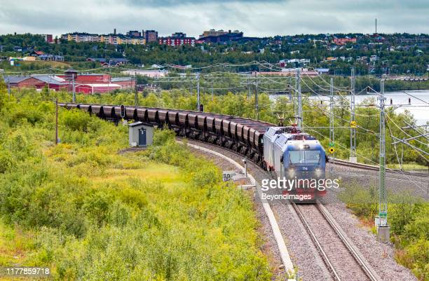 loaded lkab heavy haul iron ore train departs kiruna for norway - norrbotten province stock pictures, royalty-free photos & images