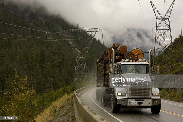 A loaded lumber truck rolls along the rainslick highway in this 2009 Whister British Columbia Canada landscape photo taken several miles north of...