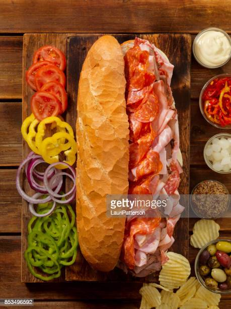 loaded party sub sandwich on a french loaf - submarine sandwich stock pictures, royalty-free photos & images