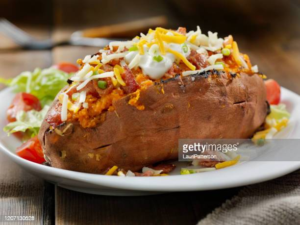 loaded, twice baked sweet potato with bacon, cheese, green onions and sour cream and a side salad - side salad stock pictures, royalty-free photos & images