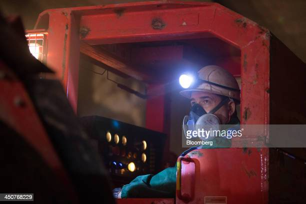 A loader wears a breathing mask and head torch as he operates a machine used to excavate diamond rock ore in OAO Alrosa's Mir diamond mine in Mirny...