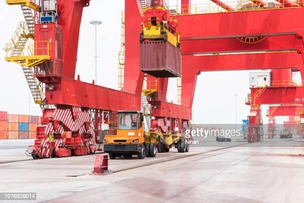 laden van een container van een schip op een voertuig dat zal het vervoer in een containerterminal - djibouti stockfoto's en -beelden