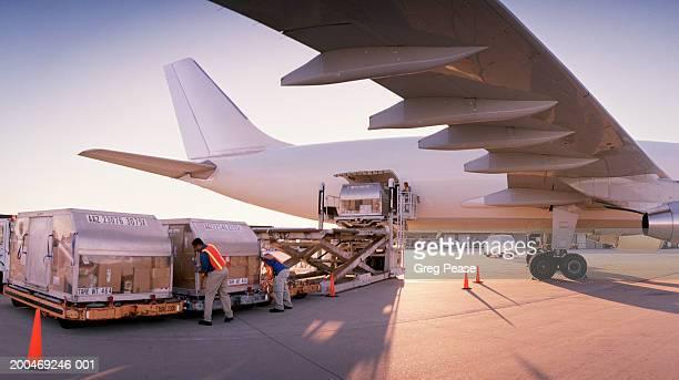 loading aeroplane with cargo, dusk - beladen stock-fotos und bilder