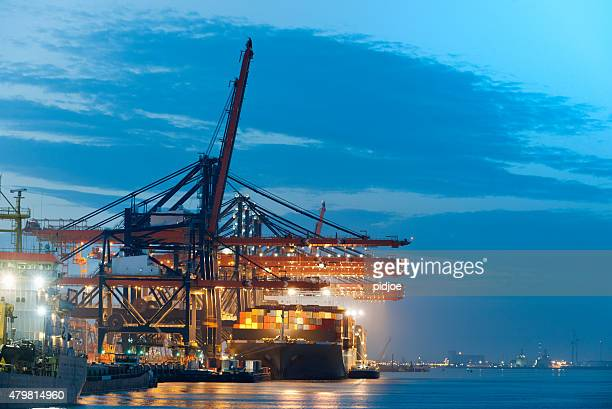 loading cargo container ship in commercial dock at twilight