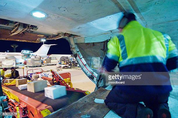loading freight into cargo hold of aircraft - offloading stock pictures, royalty-free photos & images