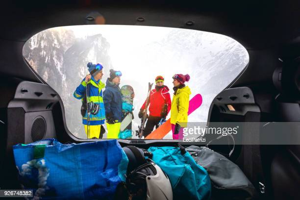 Loading the car after a skiing day in mountain - Snowboarder in the Alps - Group of friends having fun in a winter vacation