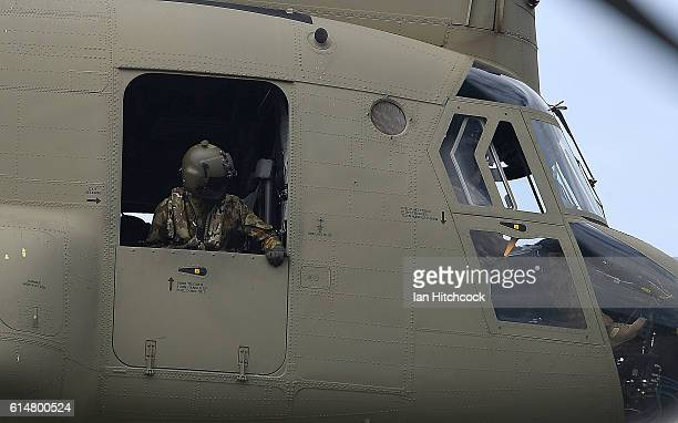 A loadmaster from an Australian Army CH47 Chinook helicopter looks from their window as it performs during the T150 Defence Force Air Show on October...