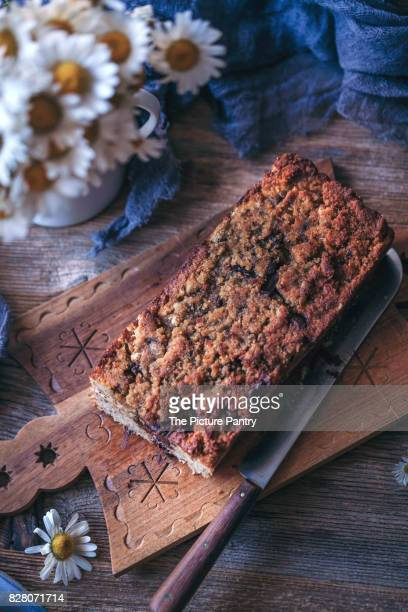 Loaf of baked chocolate chip banana bread on a wooden serving board