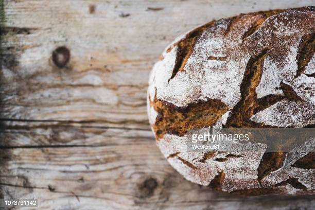 Loaf of brown bread on wood, partial view