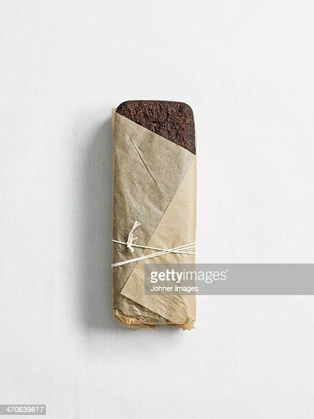 Loaf of dark bread wrapped in paper, studio shot