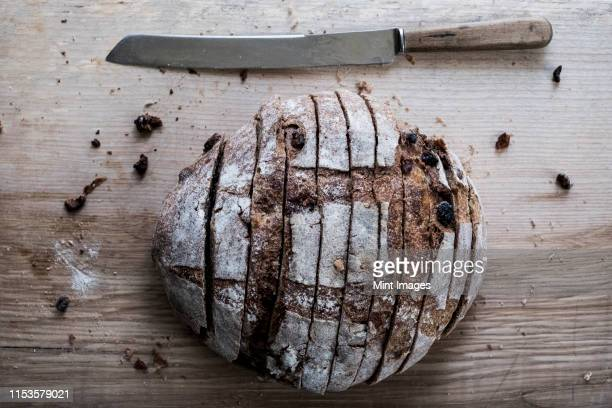 a loaf of fresh sliced brown bread on a bread board and a sharp knife - baking bread stock pictures, royalty-free photos & images