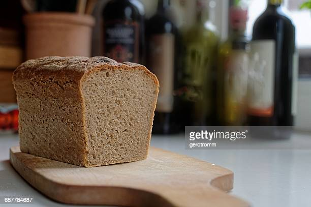 A loaf of homemade sourdough bread on a chopping board