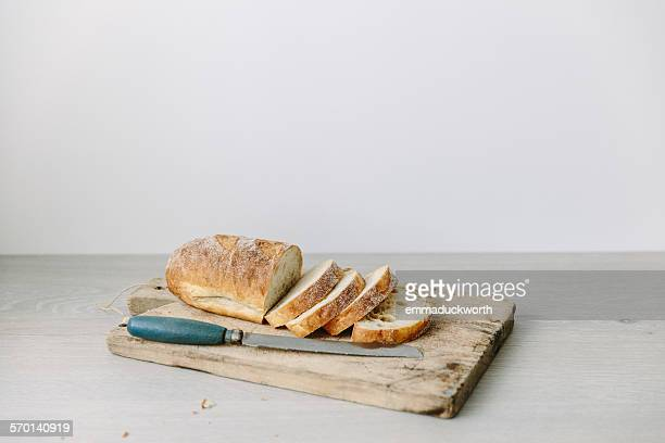 loaf of sliced bread on a chopping board - loaf of bread stock pictures, royalty-free photos & images