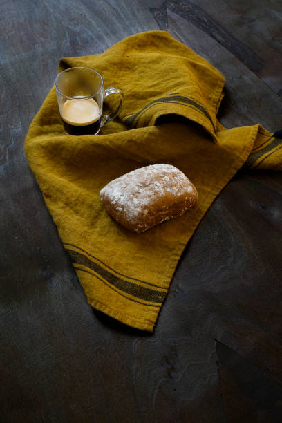 Loaf of wholemeal bread flour. a cup of coffee glasses on an ocher linen cloth laid out on a dark wooden surface. Italy.