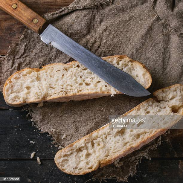 Loafs of Fresh baked artisan bread on sackcloth with vintage knife over old wooden background Overhead view Square image