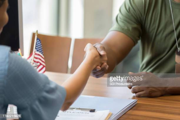 loan officer greets male soldier - veteran stock pictures, royalty-free photos & images