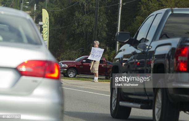 A loan protester stands in the traffic jam outside the entrance to a Republican presidential candidate Donald Trump rally at the Antique Car Museum...