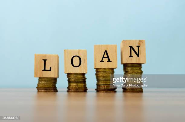 loan text written on wooden block with stacked coins - interest rate stock pictures, royalty-free photos & images