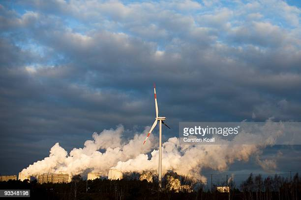 A loan wind turbine spins as exhaust plumes from cooling towers at the Jaenschwalde lignite coalfired power station which is owned by Vatenfall on...
