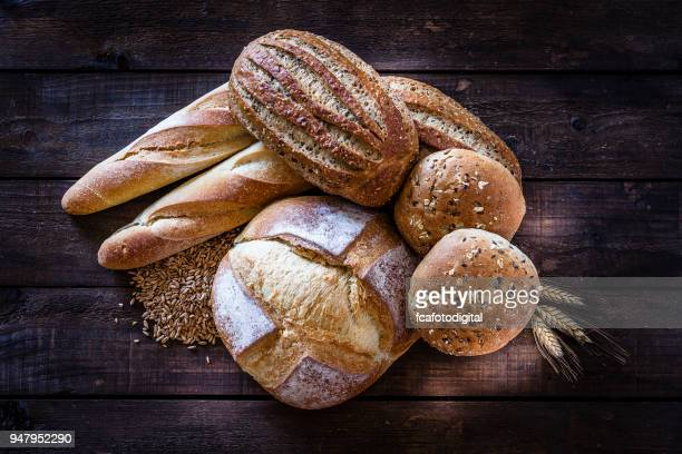 loaves of bread heap shot on rustic wooden table - bun bread stock pictures, royalty-free photos & images