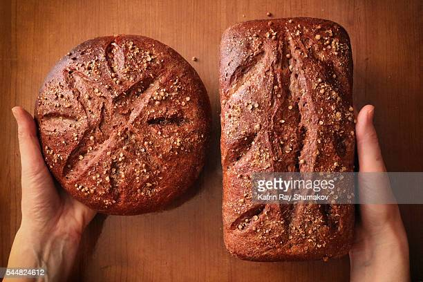 Loaves of Homemade Rye Bread in Hands