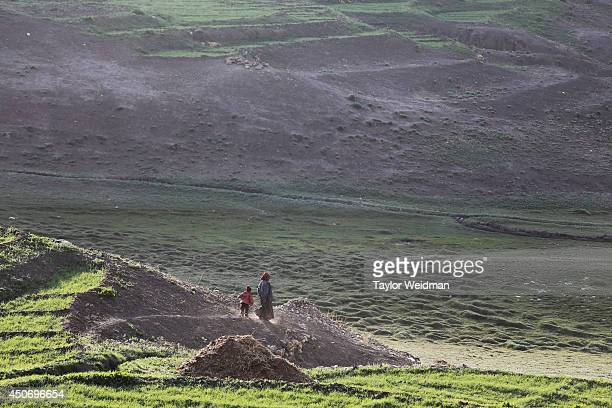Loba woman and her child walk into the fields of Dhe village. Dhe village has been facing an acute water shortage for more than a decade, with fully...
