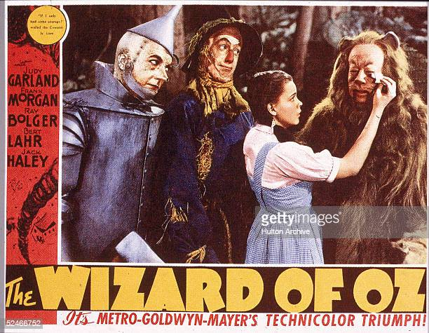 A lobby card from the film 'The Wizard Of Oz' shows a film still of a scene in which American actress Judy Garland wipes tears from the eyes of actor...